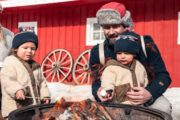 Family roasting marshmallows on a sleigh ride with Banff Trail Riders