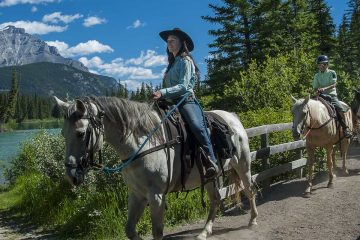 Follow your guide along the Bow River on a horseback ride with Banff Trail Riders in the Canadian Rockies