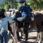 Our friendly guides will help you up onto your horse with Banff Trail Riders in the Canadian Rockies